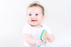 Pretty baby girl playing with a hair brush Royalty Free Stock Images