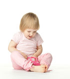 Pretty baby girl playing with a toy car Stock Image