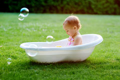 Pretty baby girl playing with water in little plastic bath outdoors in the garden Stock Photos