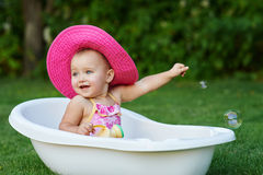 Pretty baby girl playing with water in little plastic bath outdoors in the garden.  Royalty Free Stock Photos