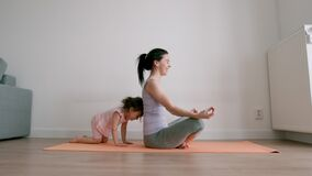 Free Pretty Baby Girl Playing With Her Mom While She Is Doing Yoga At Home Stock Images - 212918364
