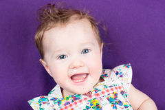 Pretty baby girl on purple blanket in floral summer dress Royalty Free Stock Image