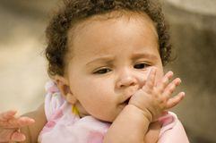 Pretty baby with hand at mouth. A pretty little baby holding her hand up to her mouth Stock Image