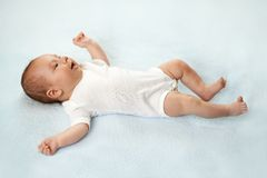 Pretty baby  is lying on the carpet Royalty Free Stock Image