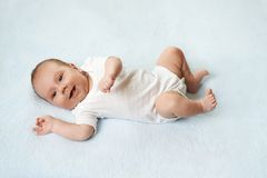 Pretty baby  is lying on the carpet Stock Image