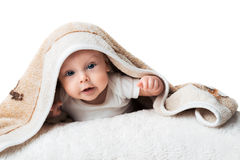 Pretty baby is lying under the carpet Stock Photos