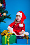 Pretty baby miss Santa sitting near Christmas tree Stock Images