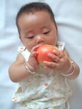 Pretty baby and red apple stock image