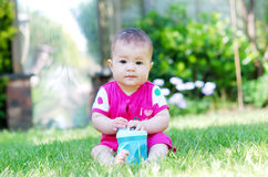A pretty baby sitting on the grass holding a bottle Stock Photography
