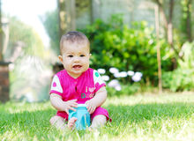A pretty baby sitting on the grass screaming holding a bottle Stock Photos