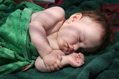 Pretty baby sleep on a bench with towels Stock Image