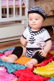 A pretty baby in a striped shirt and hats seated on the mat in the room royalty free stock photo