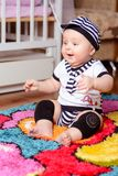 A pretty baby in a striped shirt and hats seated on the mat in the room royalty free stock photography