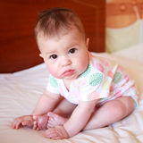 A pretty woken baby in a vest sitting in bed Royalty Free Stock Photos