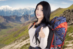 Pretty backpacker showing thumb up Royalty Free Stock Photo