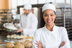 Pretty baker smiling at camera. In the kitchen of the bakery Stock Photo