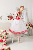 Pretty ballerina holding flowers. Pretty ballerina in stage costume, holding a bouquet of spring flowers. Retro dress. She dreams. She`s a slender girl Stock Photo