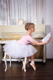 Pretty ballerina with notes in her hands Royalty Free Stock Image
