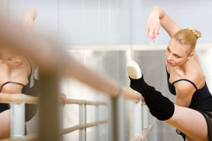 Pretty ballerina stretches herself near barre Royalty Free Stock Photos