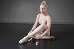Pretty ballerina tying the ribbon on her ballet slippers Royalty Free Stock Photos