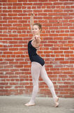 Pretty ballet girl posed in front of red brick wall. Beautiful and young ballerina gracefully posed in Ecarte while facing left Royalty Free Stock Photo