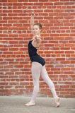 Pretty ballet girl posed in front of red brick wall. stock photography