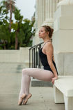 Pretty ballet girl posed on white bench royalty free stock images