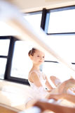 Pretty Ballet Girl Stretching her Leg Using a Bar Stock Photography
