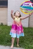 Vertical frontal photo of little girl in rainbow coloured summer dress throwing multicolored beach ball royalty free stock photography