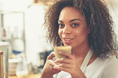 Pretty barista drinking warm tasty latte in cafeteria Stock Photo