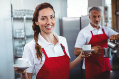 Pretty barista holding cups of coffee with colleague behind Stock Photos