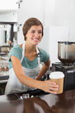 Pretty barista holding disposable cup Stock Photography