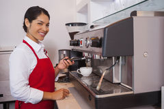 Pretty barista making coffee smiling at camera Stock Images
