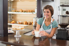 Pretty barista offering cup of coffee smiling Royalty Free Stock Image