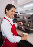 Pretty barista pouring milk into cup of coffee Royalty Free Stock Photos