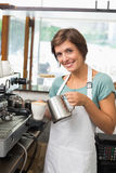 Pretty barista pouring milk into cup of coffee Stock Photos