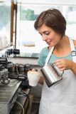 Pretty barista pouring milk into cup of coffee Stock Photo
