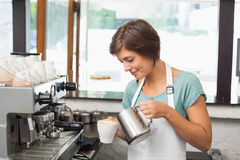 Pretty barista pouring milk into cup of coffee Stock Photography