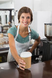 Pretty barista smiling at camera holding disposable cup Royalty Free Stock Photos