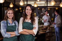 Pretty baristas standing with arms crossed. In the bar Royalty Free Stock Image