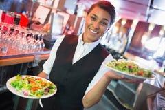 Pretty barmaid holding plates of salads Stock Image
