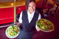 Pretty barmaid holding plates of salads Royalty Free Stock Photography