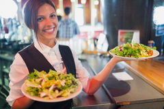 Pretty barmaid holding plates of salads Royalty Free Stock Photos