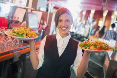 Pretty barmaid holding plates of salads Stock Image