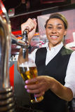 Pretty barmaid pulling pint of beer Stock Photos