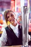 Pretty barmaid pulling pint of beer Royalty Free Stock Image