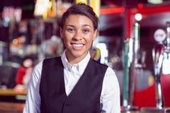 Pretty barmaid smiling at camera Stock Image