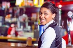 Pretty barmaid smiling at camera Royalty Free Stock Image