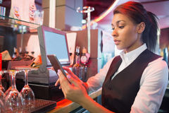 Pretty barmaid using touchscreen till Stock Image