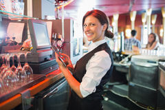 Pretty barmaid using touchscreen till Stock Photography